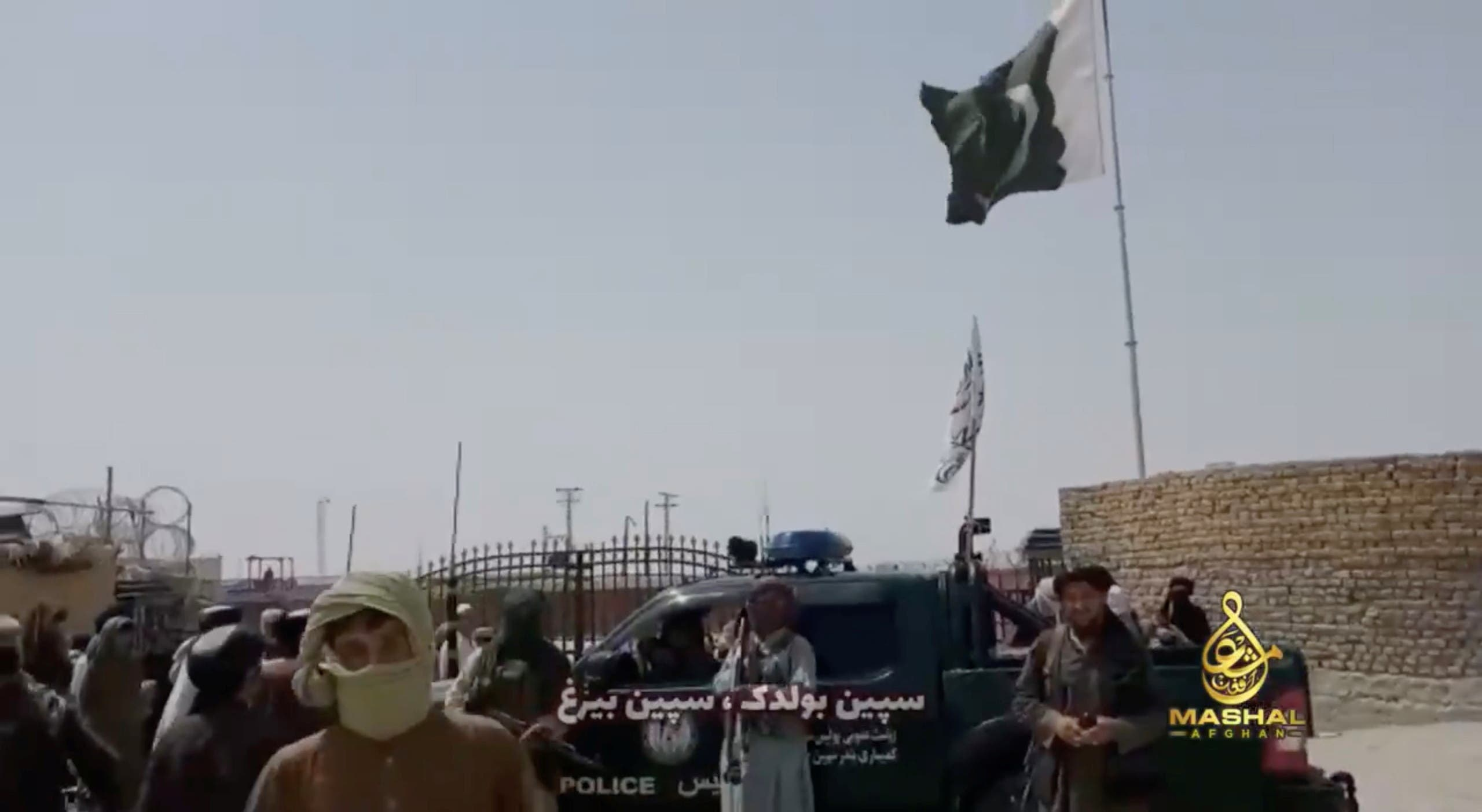 People stand in front of a vehicle as an Islamic Emirate of Afghanistan and a Pakistan's flag flutter in front of the friendship gate of Afghanistan and Pakistan at the Wesh-Chaman border crossing, Spin Boldak, Afghanistan July 14, 2021, in this screen grab obtained from a video. (Reuters)