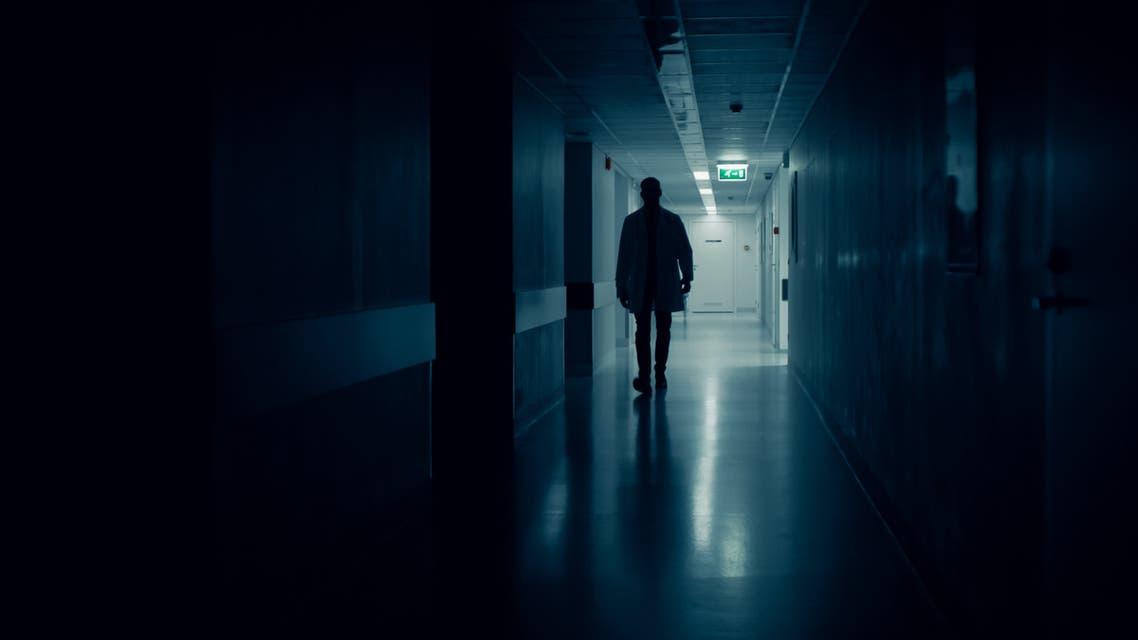 Medical Doctor Silhouette Walks in Dark Part of the Hospital Corridor. stock photo