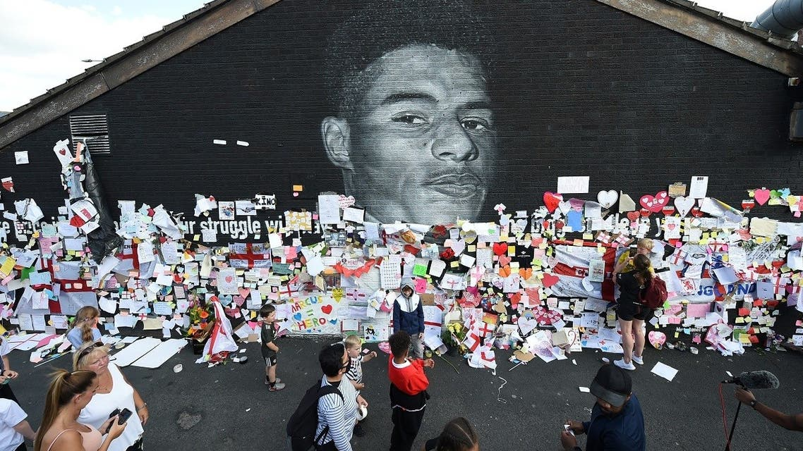 People look at messages of support on the Marcus Rashford mural in Withington, Manchester, Britain, on July 13, 2021, after it was defaced following the Euro 2020 Final between Italy and England. (Reuters)