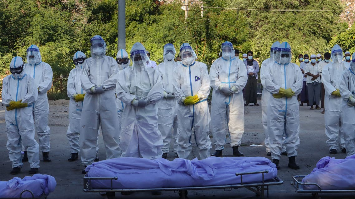 Volunteers wearing personal protective equipment (PPE) pray in front of bodies of people who died from the Covid-19 coronavirus during their funeral at a cemetery in Mandalay on July 14, 2021. (File photo:AFP)