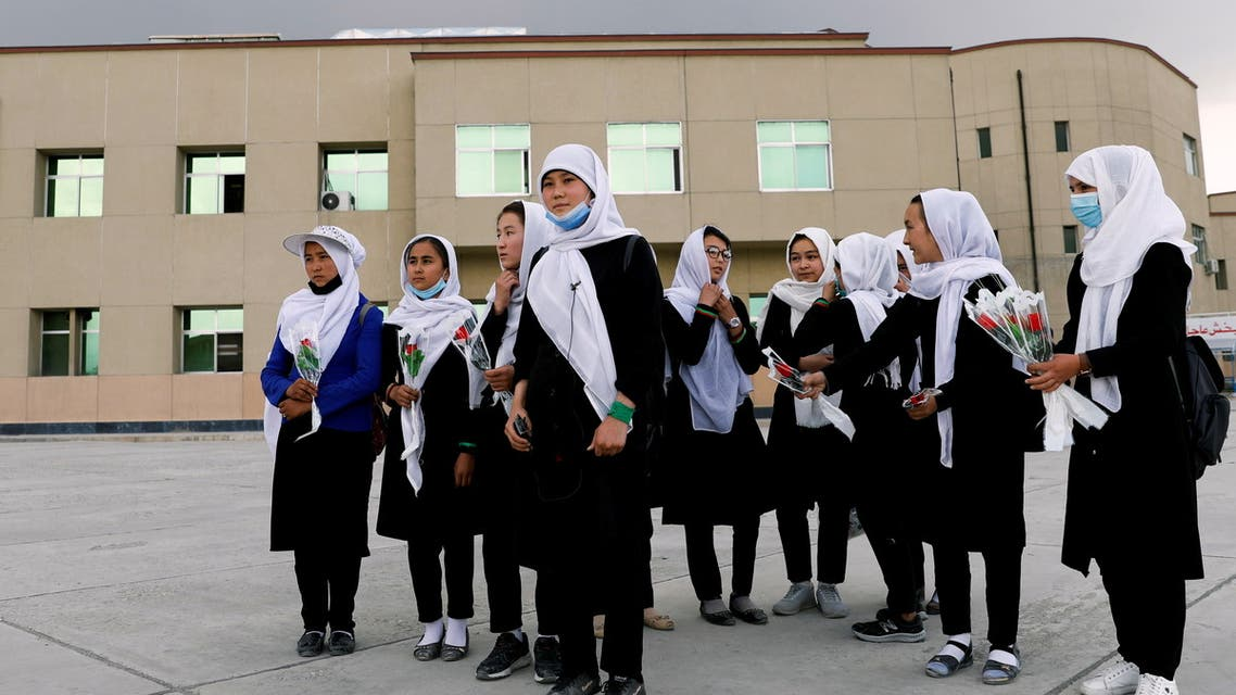 Schoolgirls hold flowers as they arrive to visit students who were injured in a car bomb blast outside a school on Saturday, at a hospital in Kabul, Afghanistan May 10, 2021.REUTERS/Stringer