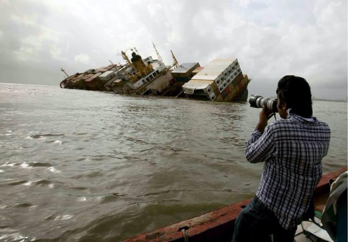 Reuters photographer Danish Siddiqui takes pictures from a fishing boat of the damaged cargo ship MSC Chitra in the Arabian Sea off the Mumbai coast, August 9, 2010. (Reuters)