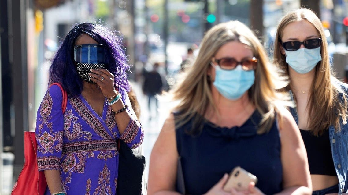 People wearing face protective masks walk on Hollywood Blvd during the outbreak of the coronavirus disease (COVID-19), in Los Angeles. (Reuters)