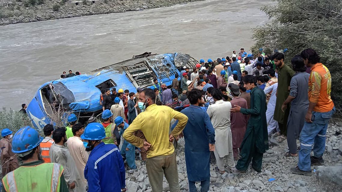 Rescue workers and onlookers gather around a wreck after a bus plunged into a ravine following a bomb explosion, which killed 12 people including 9 Chinese workers, in Kohistan district of Khyber Pakhtunkhwa province on July 14, 2021. (AFP)