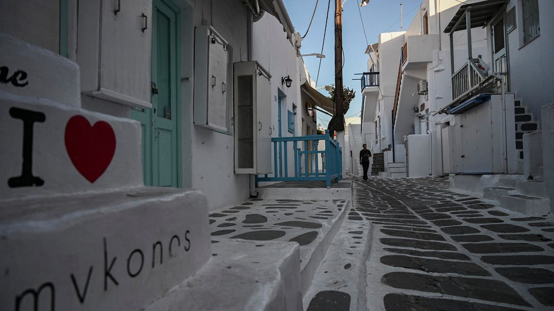 A man walks in the empty alleys of the Greek Cycladic island of Mykonos, on May 13, 2020. (AFP)