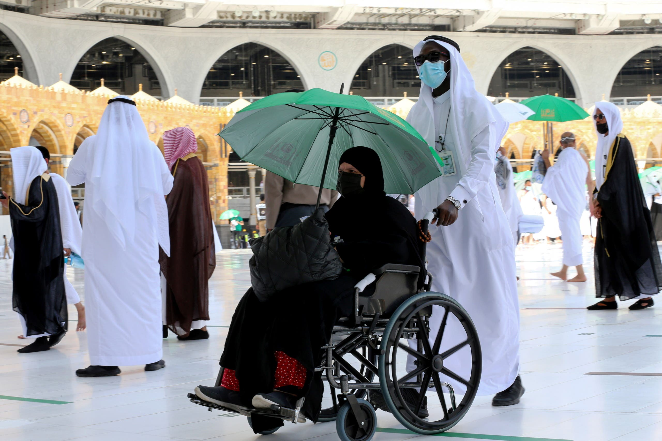 A man pushes a wheelchair for a Muslim pilgrim in the Grand Mosque in the holy city of Mecca, Saudi Arabia July 17, 2021. (Reuters)