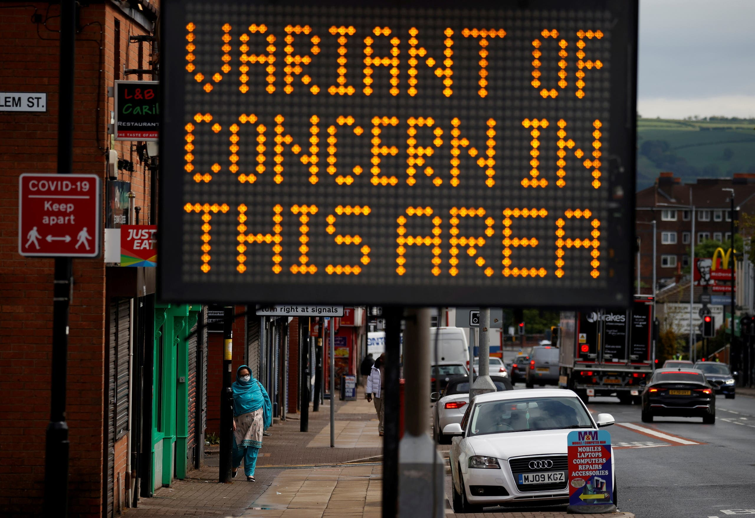 A woman walks past an information sign amid the outbreak of the coronavirus disease (COVID-19) in Bolton, Britain, May 17, 2021. (File Photo: Reuters)