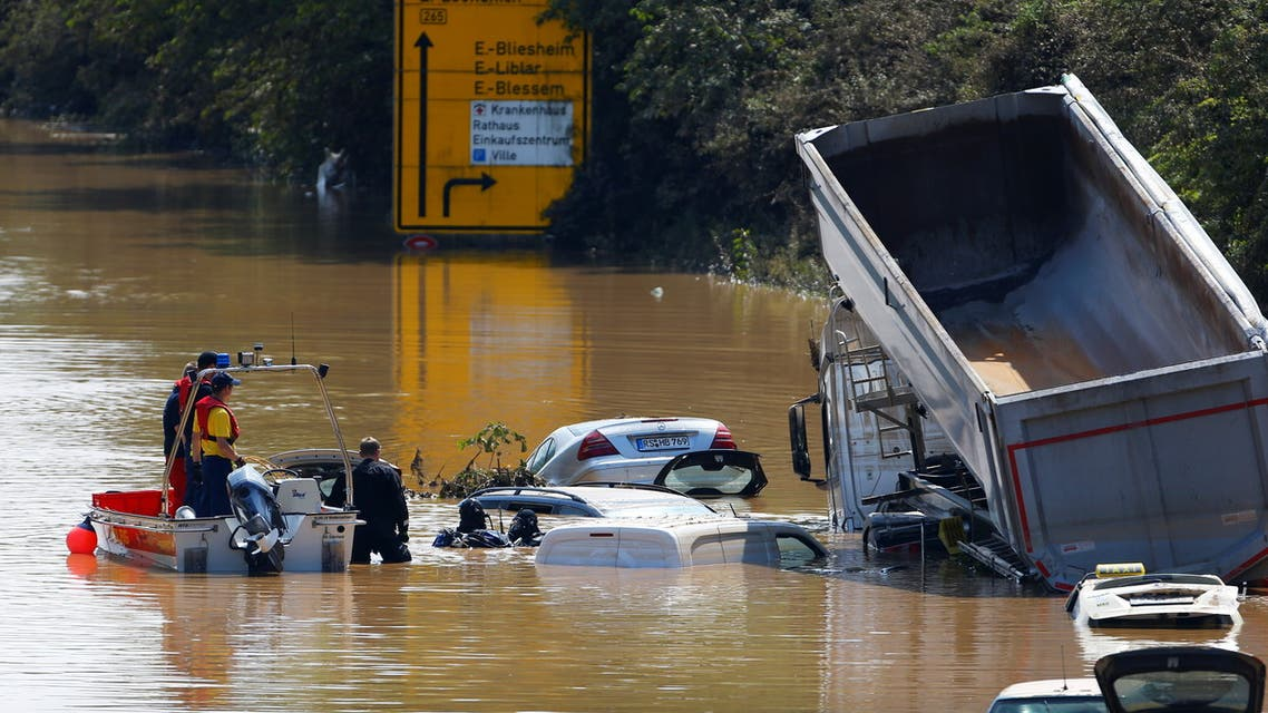 A police officer and a member of the Bundeswehr forces look at partially submerged cars on a flooded road following heavy rainfalls in Erftstadt-Blessem, Germany, July 17, 2021. REUTERS/Thilo Schmuelgen