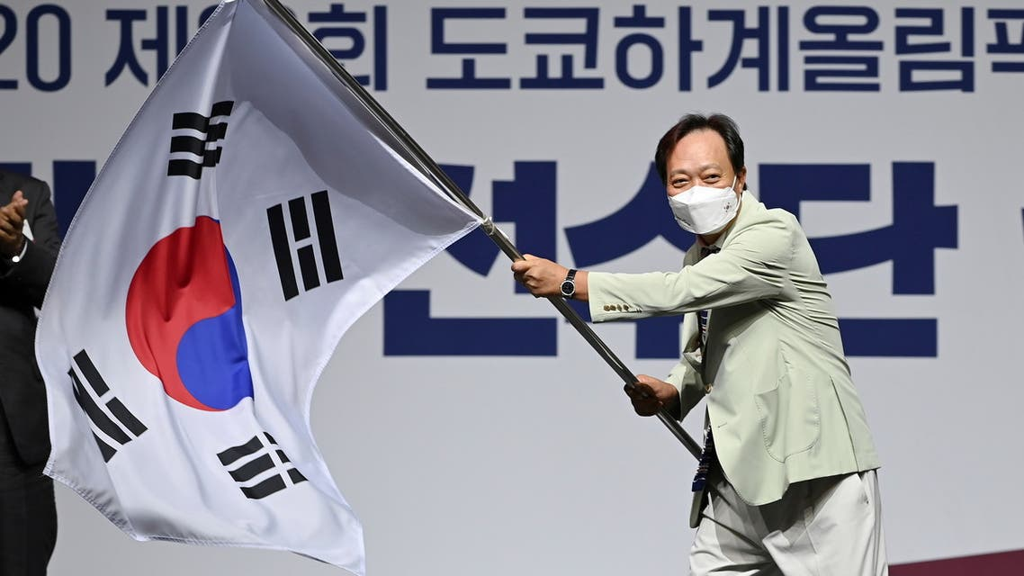 Head of South Korea's delegation to Tokyo 2020 Olympic Games, Jang In-hwa, waves the national flag during an inaugural ceremony ahead of the team's departure for Japan, in Seoul, South Korea July 8, 2021. Jung Yeon-je/Pool via REUTERS