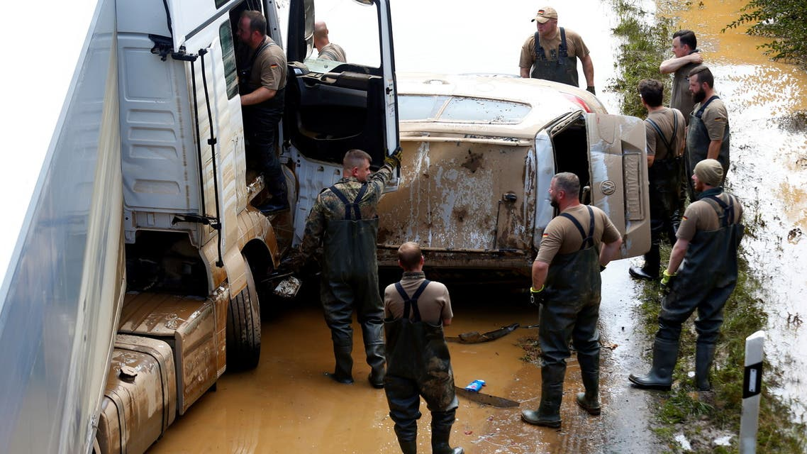 Members of the Bundeswehr forces recover cars on a flooded road following heavy rainfalls in Erftstadt-Blessem, Germany, July 17, 2021. (Reuters)