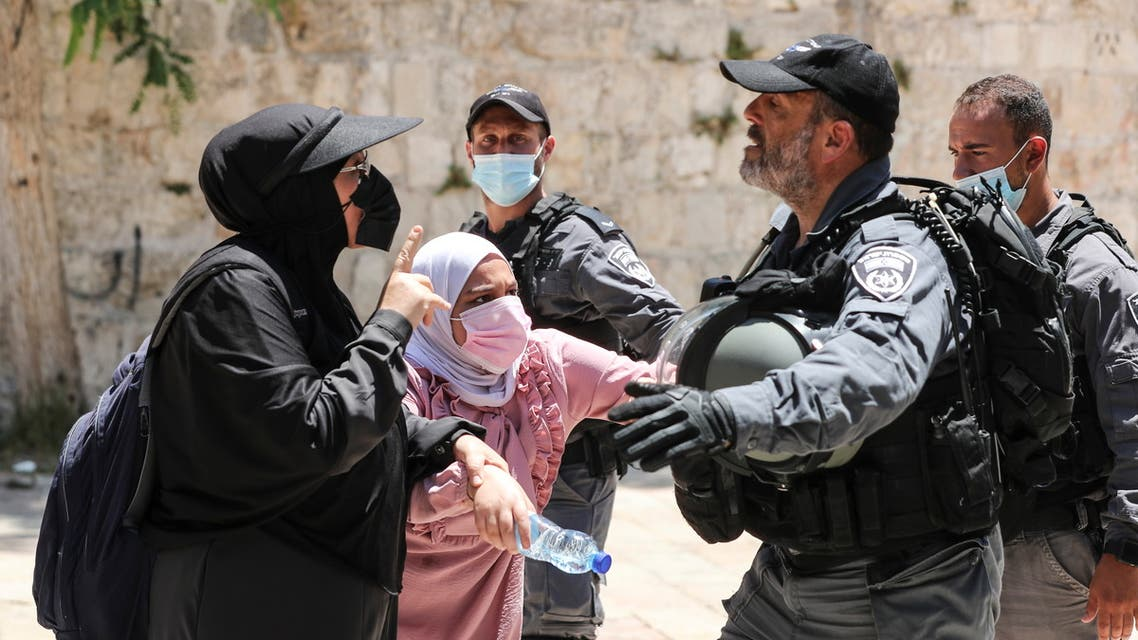 Palestinian women argue with an Israeli security force member after brief clashes erupted between Israeli police and Palestinians at al-Aqsa Mosque over visits by Jews on the Tisha B'Av fast day to the compound known to Muslims as Noble Sanctuary and to Jews as Temple Mount, in Jerusalem's Old City, July 18, 2021. (Reuters)