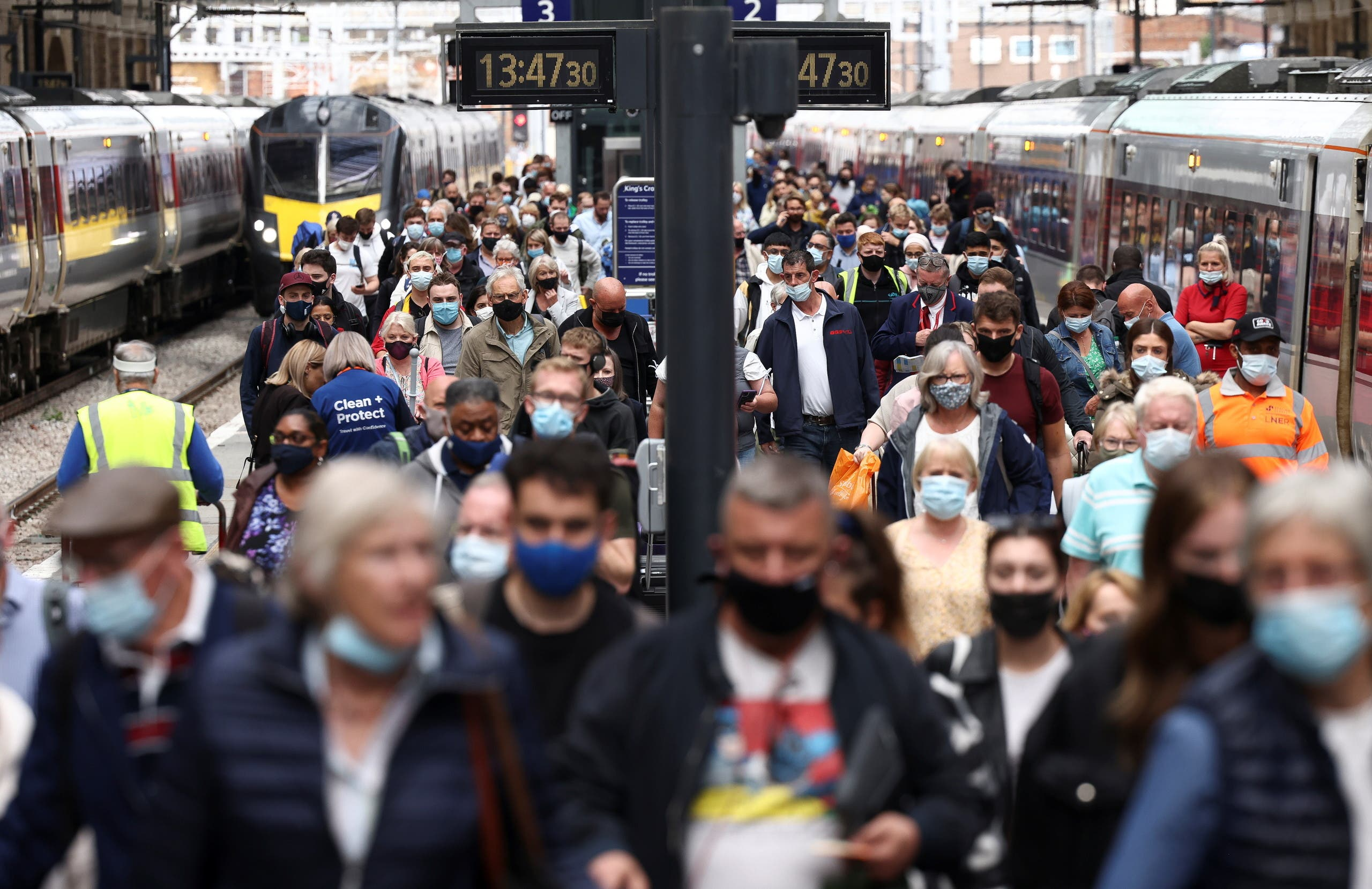 People wearing protective face masks walk along a platform at King's Cross Station, amid the coronavirus disease (COVID-19) outbreak in London, Britain, July 12, 2021. (Reuters)