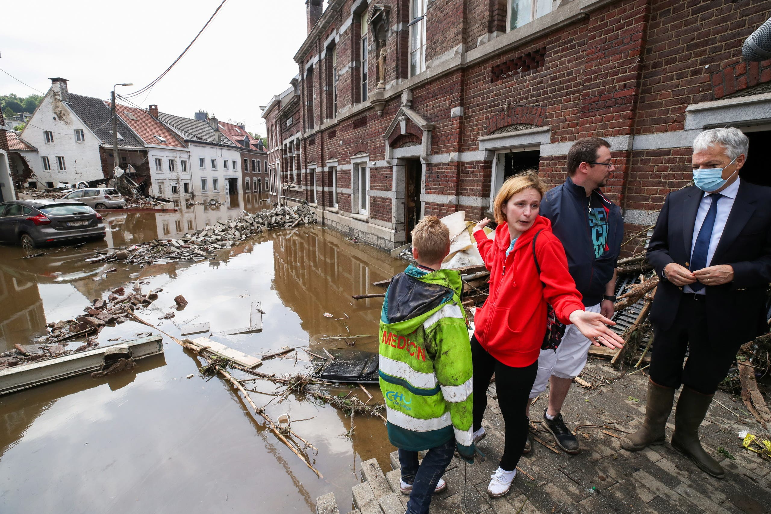 European Commissioner for Justice Didier Reynders speaks with Madeline Brasseur, 37, Paul Brasseur, 42, and their son Samuel, 12, at an area affected by floods, following heavy rainfalls, in Pepinster, Belgium, July 17, 2021. (Reuters)