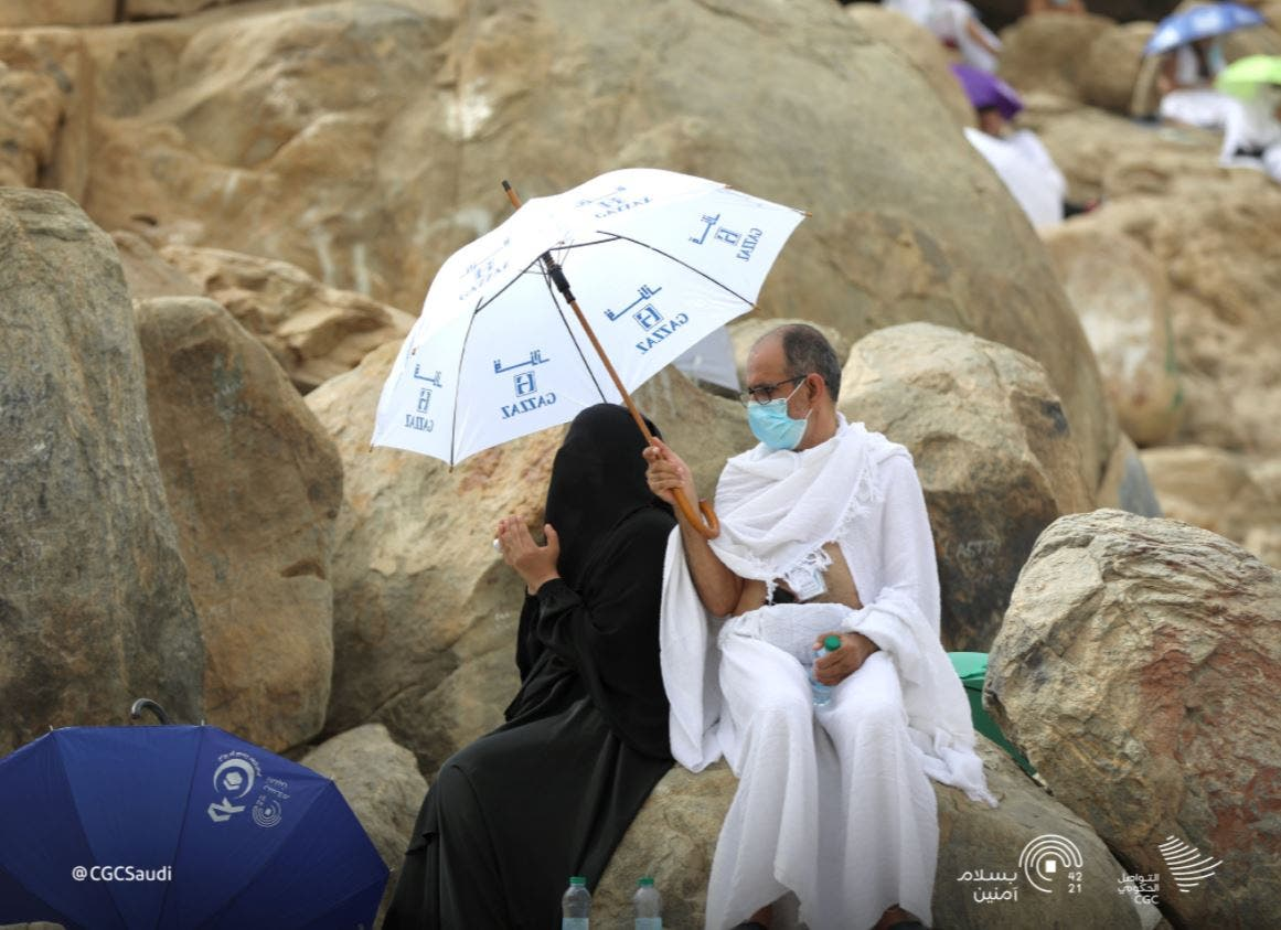 A man holds an umbrella over the head of his wife as she prays on Mount Arafat. (Photo Courtesy: Ministry of Media)
