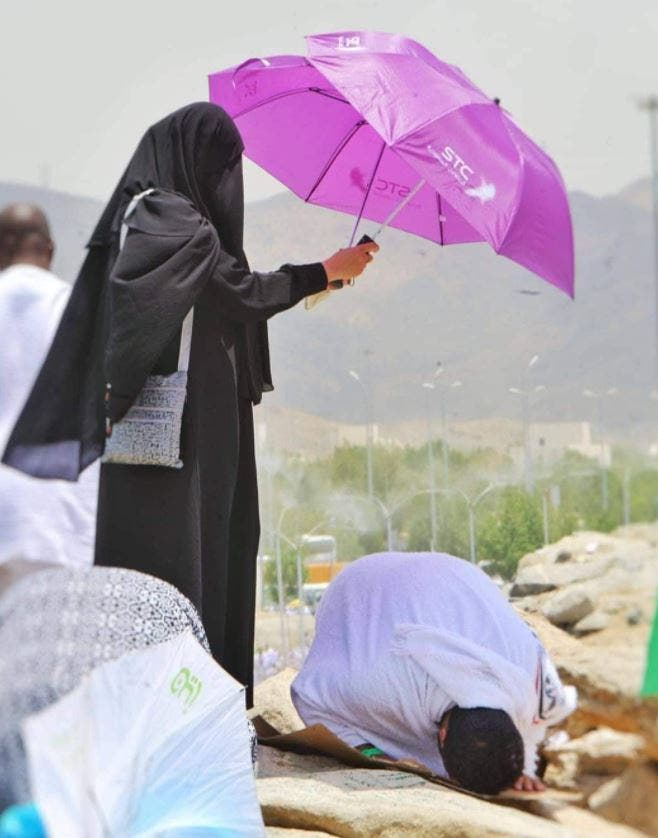 A woman holds an umbrella above her husband as he prays on Mount Arafat. (Twitter)