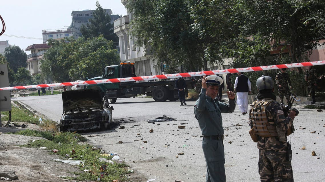 Afghan security personnel stand guard near a charred vehicle from which rockets were fired that landed near the Afghan presidential palace in Kabul on July 20, 2021. (AFP)