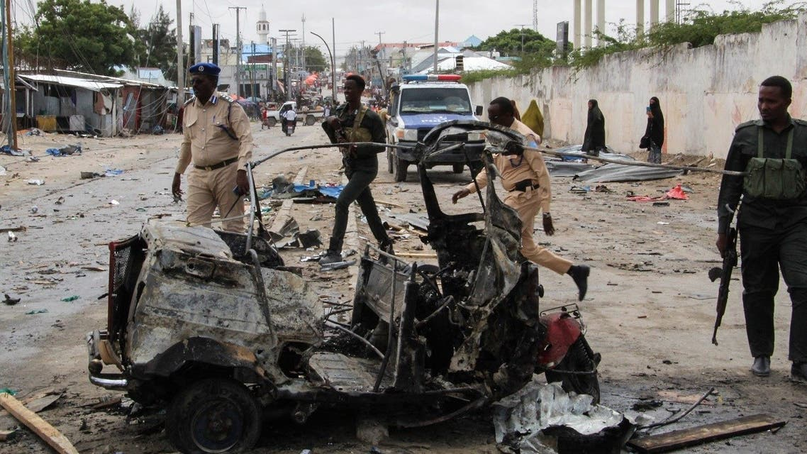 Police officers patrol by the wreckage of a car at the scene of suicide car bomb attack that targeted the city's police commissioner in Mogadishu, on July 10, 2021. (AFP)