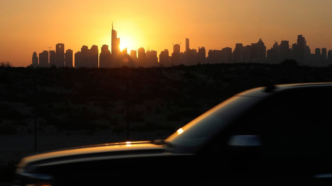 The sunlight reflects on a car glass as it sets behind the city skyline at the Marina and Jumeirah Lake Towers districts in Dubai, United Arab Emirates, Friday, Feb. 26, 2021. (AP Photo/Kamran Jebreili)