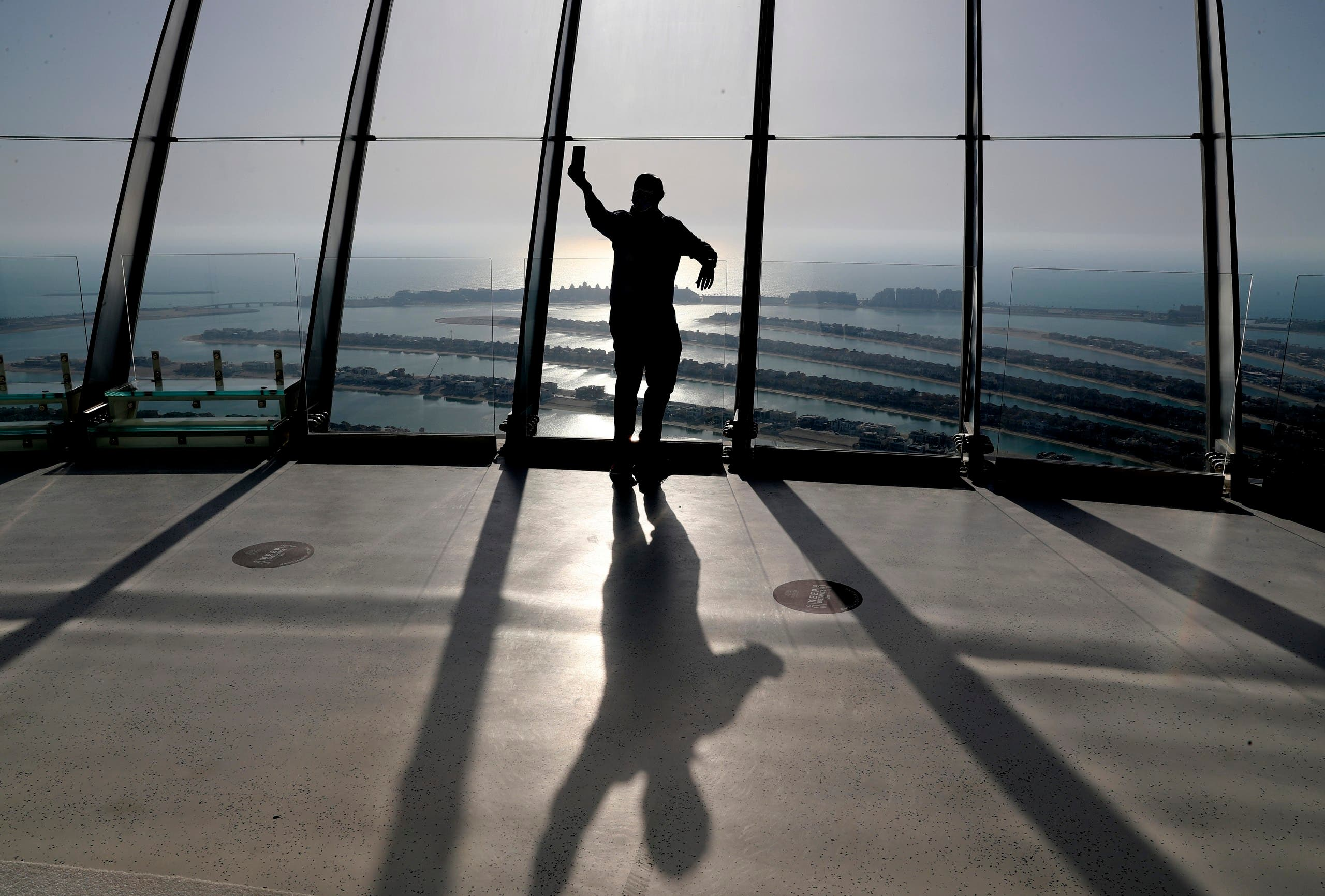 A man takes selfie on the observation deck of The View at The Palm Jumeirah in Dubai, United Arab Emirates, Tuesday, April 6, 2021. (AP)