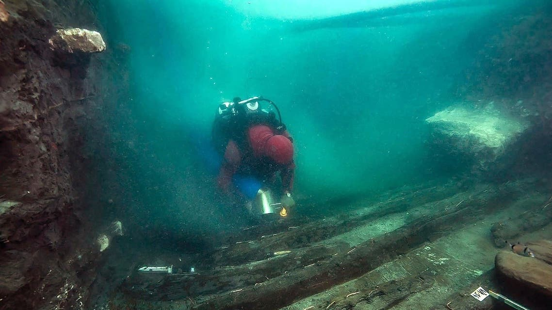 A handout picture released on July 19, 2021 shows a diver exploring the hull of a military vessel discovered in the sunken city of Thonis-Heracleion in Abu Qir bay, on Egypt's northern Mediterranean coast. (Egyptian Ministry of Antiquities/AFP)