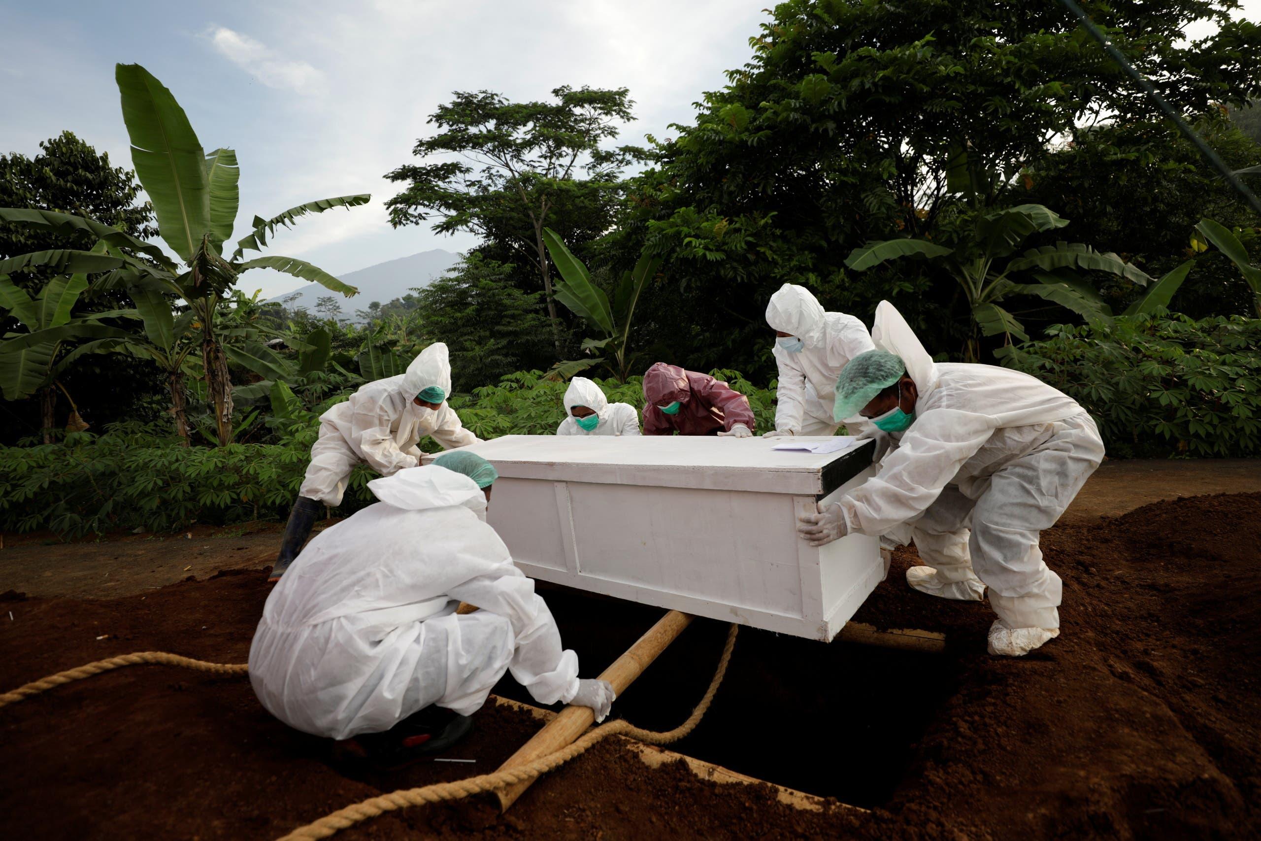دفن أحد المتوفين بكورونا في جزيرة جاوة في إندونيسيا