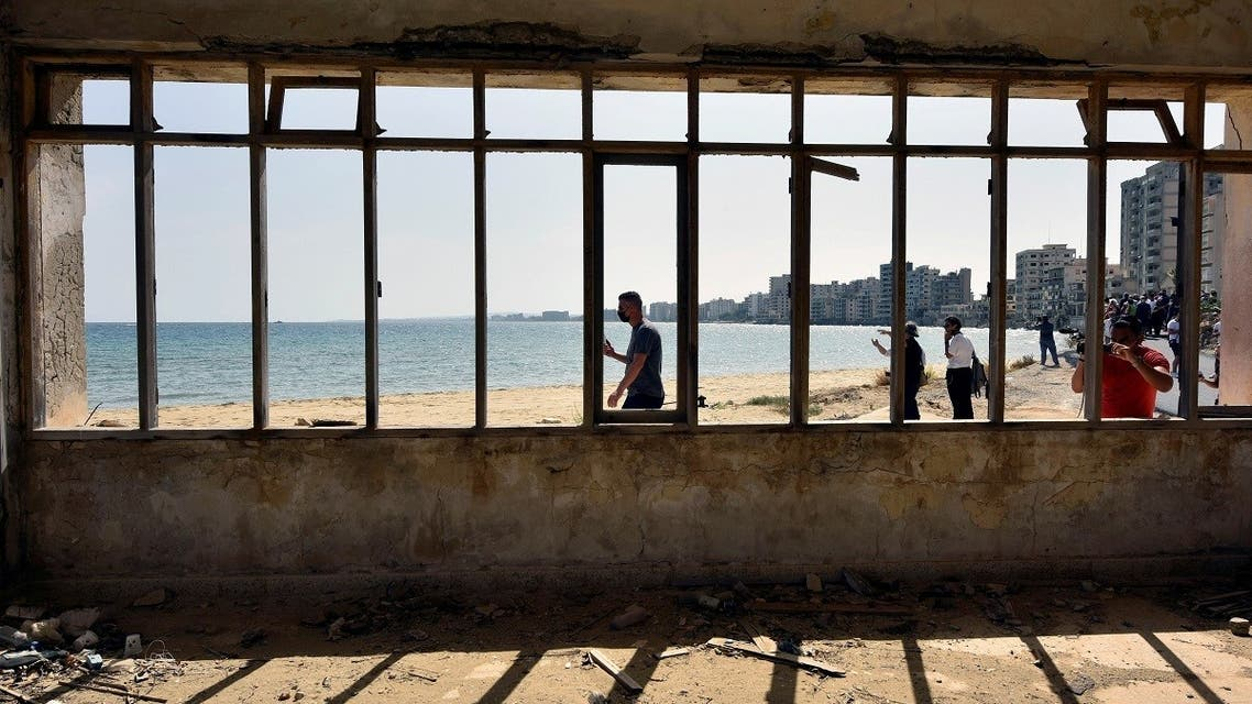 People walk on a beach inside an area fenced off by the Turkish military since 1974 in the abandoned coastal area of Varosha, a suburb of the town of Famagusta in Turkish-controlled northern Cyprus. (File photo: Reuters)