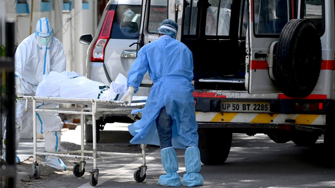 Hospital staff take out a body from an ambulance at a mortuary in New Delhi on May 24, 2021, as India passes more than 300,000 deaths from coronavirus pandemic.