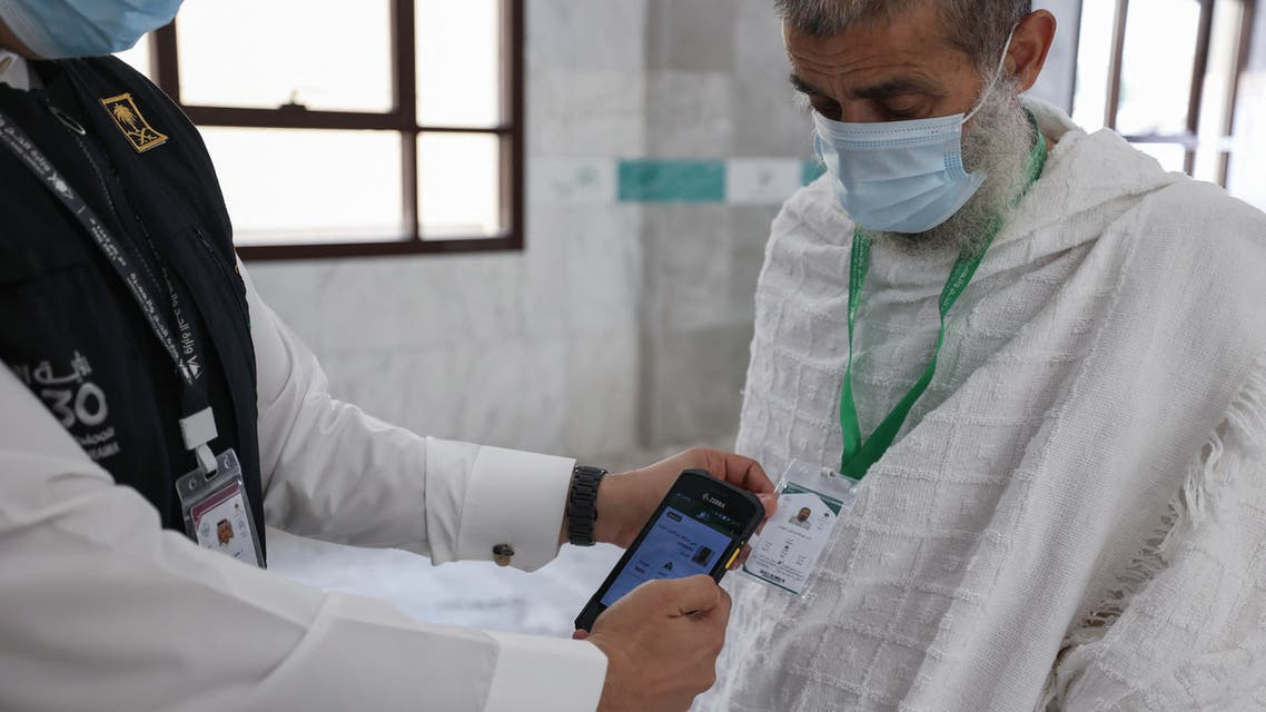 A Saudi member of staff scans a pilgrim's hajj card, allowing contactless access to religious sites, accommodation and transport, at a reception centre in Mecca on July 18, 2021. (AFP)