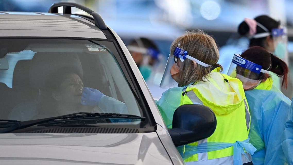 A health worker (R) conducts a COVID-19 test at the St. Vincent's Hospital drive-through testing clinic at Bondi Beach in Sydney June 27, 2021, on the first full day of a two-week coronavirus lockdown to contain an outbreak of the highly contagious Delta variant.