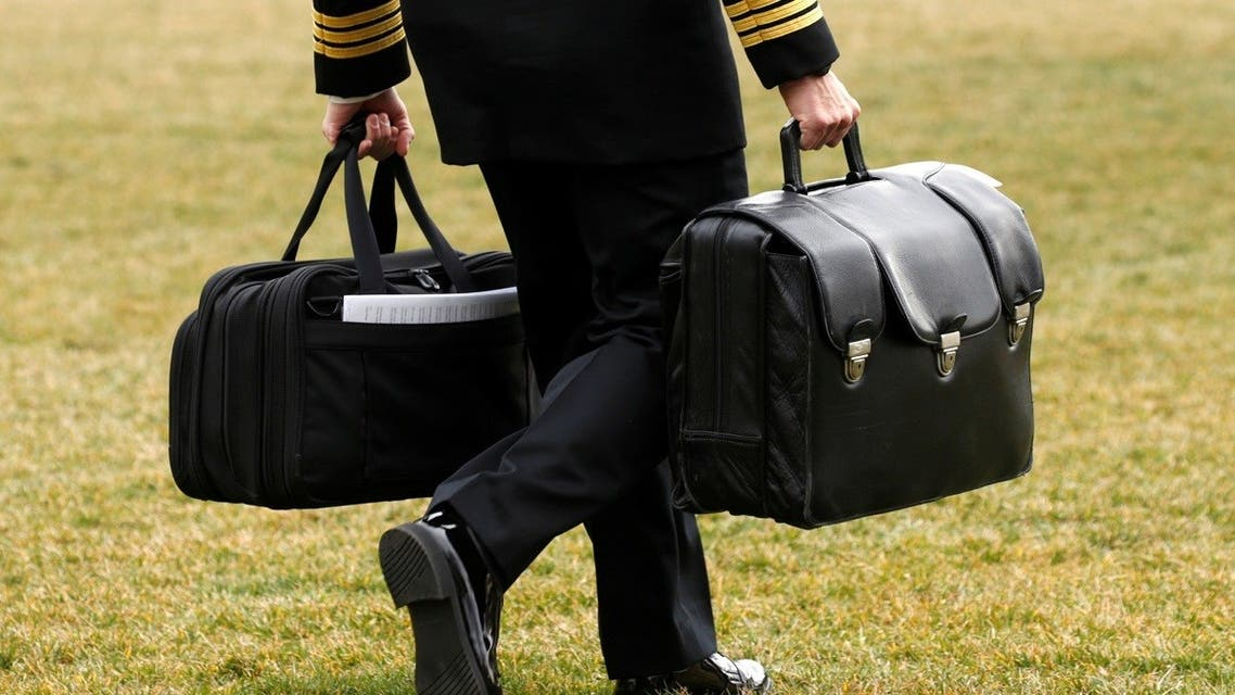 A military aide, carrying the football containing launch codes for nuclear weapons, accompanies former US President Donald Trump onto Marine One, Feb. 3, 2017. (Reuters)