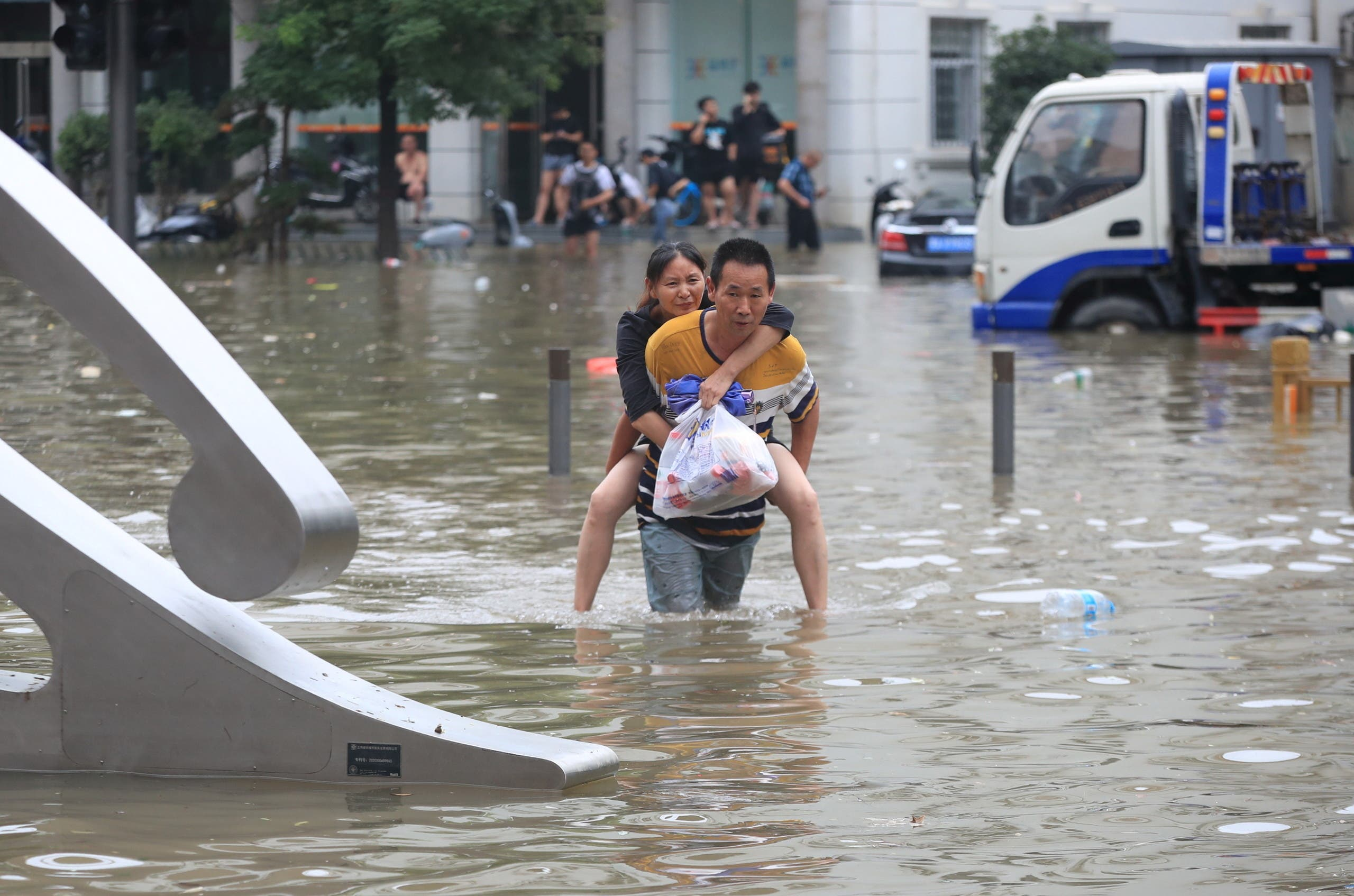 A resident wearing a rain cover stands on a flooded road in Zhengzhou, Henan province, China July 20, 2021. (Reuters)