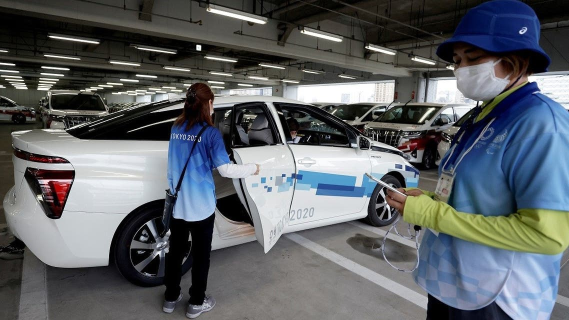A staff member gets into a Toyota Mirai fuel cell electric vehicle (FCEV) during a demonstration of the transport operation support system for Tokyo 2020 Olympic Games personnel, in Tokyo, Japan, on July 1, 2021. (Reuters)