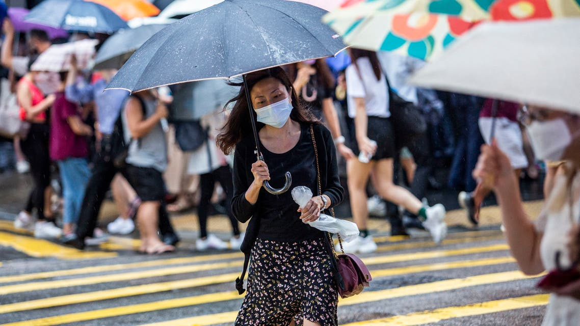 A woman (C) holds an umbrella as she crosses a road in Hong Kong on July 20, 2021, as weather patterns from Typhoon Cempaka brings heavy rain to the city. (File photo: AFP)