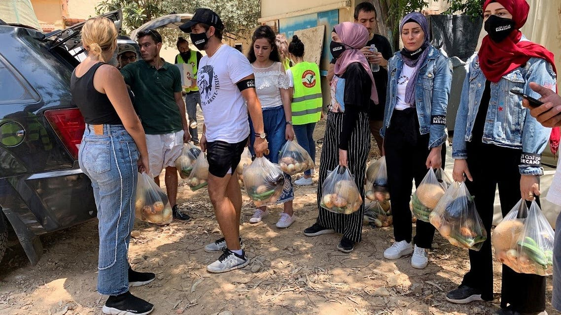 Volunteers from Base Camp, carry bags of vegetables to be distributed to people in need in Beirut, Lebanon, on July 1, 2021. (Reuters)