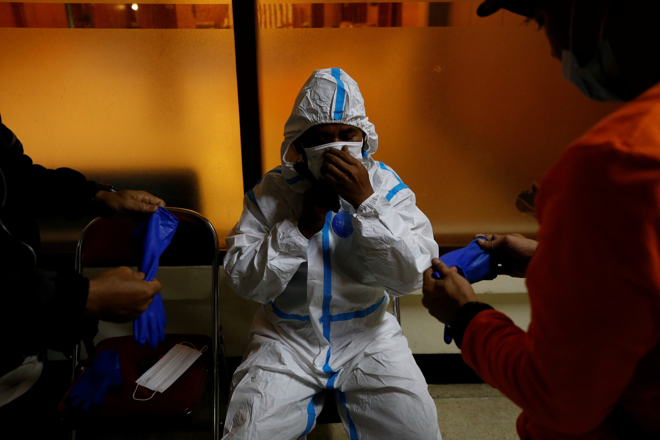 Komarudin, 48, a volunteer undertaker, prepares his personal protective equipment at the group's headquarters before collecting the body of a person who passed away due to complications related to COVID-19 whilst isolating at home in Bogor, West Java province, Indonesia, July 11, 2021. (Reuters)