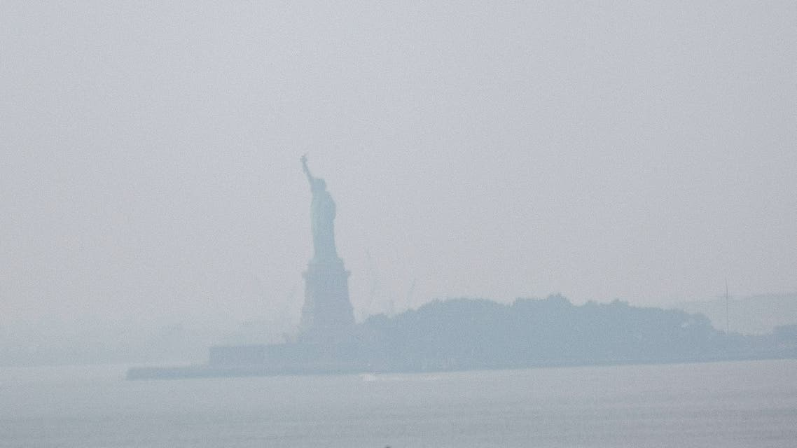 NEW YORK, NEW YORK - JULY 20: The Statue of Liberty sits behind a cloud of haze on July 20, 2021 in New York City. According to data from the National Oceanic and Atmospheric Administration, wildfire smoke from the west has arrived in the tri-state area creating decreased visibility and a yellowish haze in many areas. Spencer Platt/Getty Images/AFP