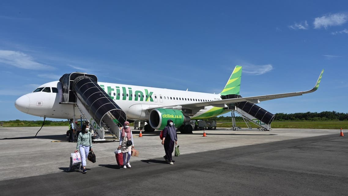 Passengers walk away from an Airbus A320-200 plane that belongs to Citilink airline upon arriving at the Fatmawati Soekarno airport in Bengkulu on April 25, 2021. (File photo: AFP)