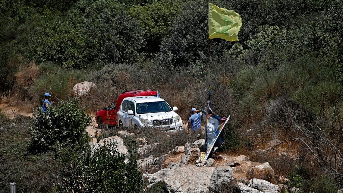 UN peacekeepers stand next to a Hezbollah flag raised on the Lebanese side of the border fence with Israel, near the northern Israeli settlement of Shtula on July 20, 2021. (AFP)