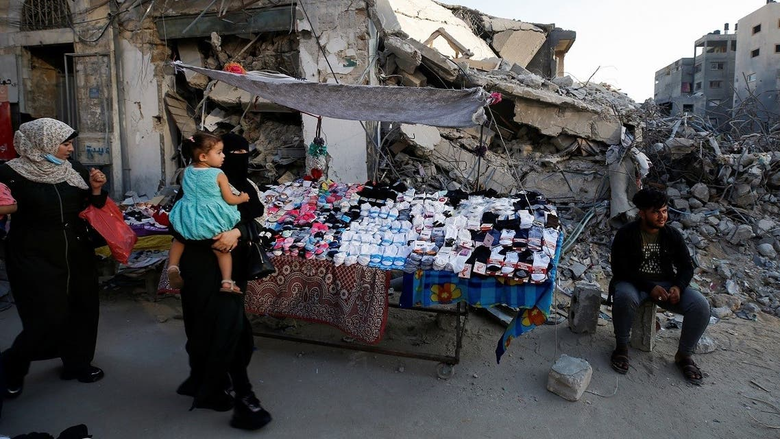 A Palestinian sells socks on a stall near the rubble of his old store that has been destroyed in an Israeli air strike, ahead of Eid Al-Adha holiday, in Gaza City, on July 14, 2021.  (Reuters)
