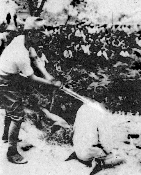 صورة لجندي ياباني وهو يحاول قطع رأس أحد الصينيين بالحرب الصينية اليابانية
