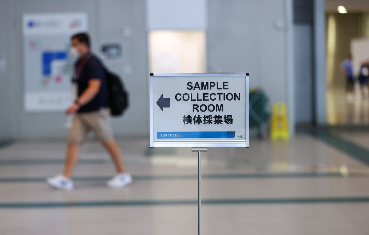 A sign is seen as a man walks to the PCR sample collection room at the main press center ahead of the Tokyo 2020 Olympic Games that were postponed to 2021 due to the coronavirus disease (COVID-19) pandemic, in Tokyo, Japan, July 22, 2021. (Reuters)