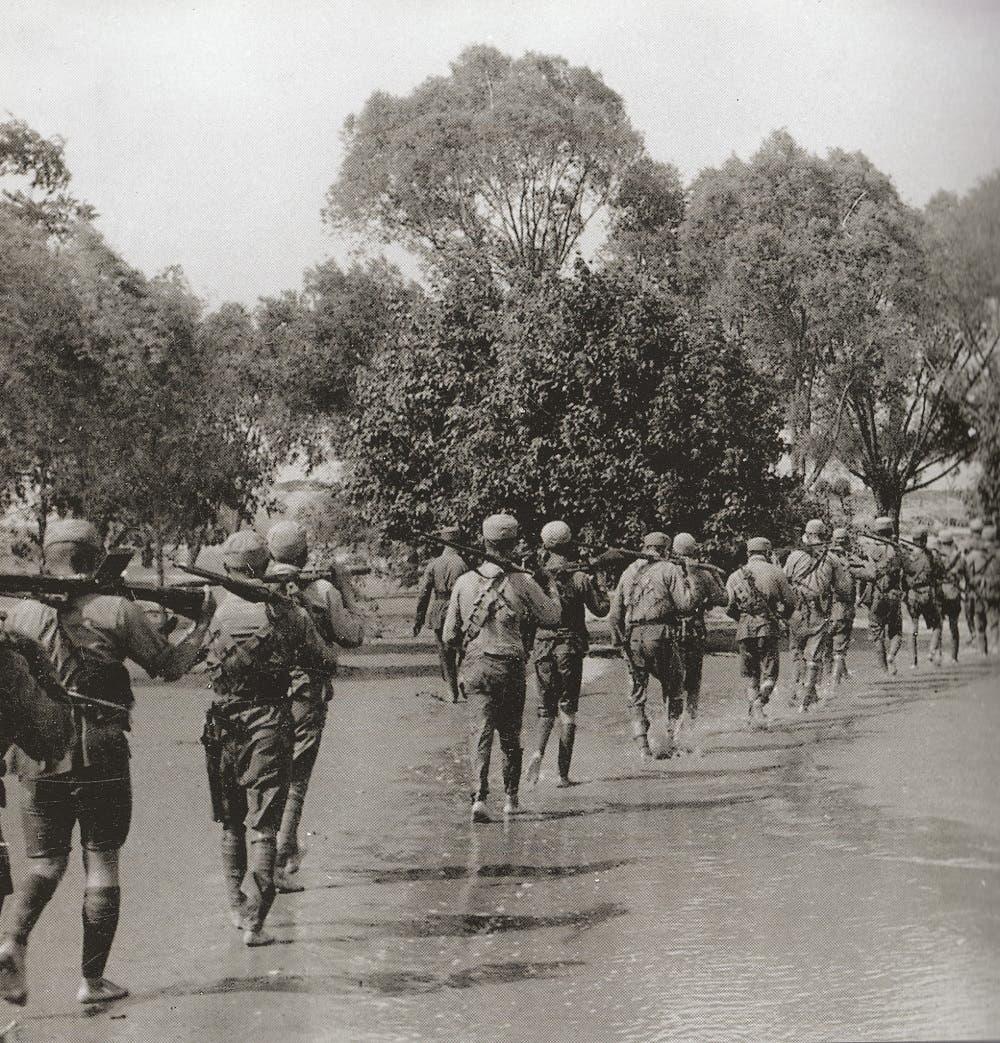 عدد من الجنود القوميين الصينيين وهو يسيرون بمنطقة غمرتها مياه النهر الأصفر