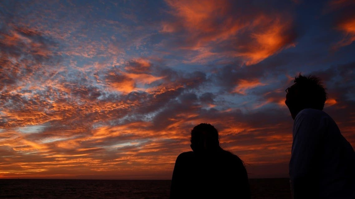 Crew members on the migrant search and rescue ship Sea-Watch 3 watch the sunset as the vessel sails off the Gulf of Hammamet off the coast of Tunisia in the central Mediterranean. (File photo: Reuters)