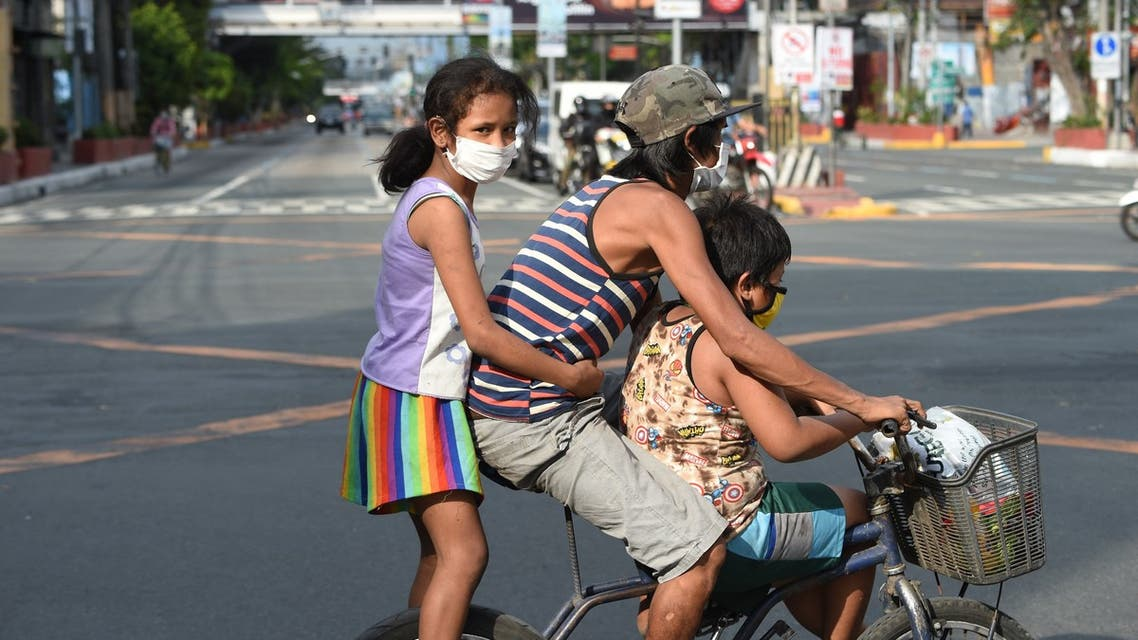 A father with his children aboard their bicycle crosses an almost empty road in Manila on March 20, 2020, after the government imposed an enhanced community quarantine against the rising numbers of COVID-19 coronavirus infections.. (File photo: AFP)