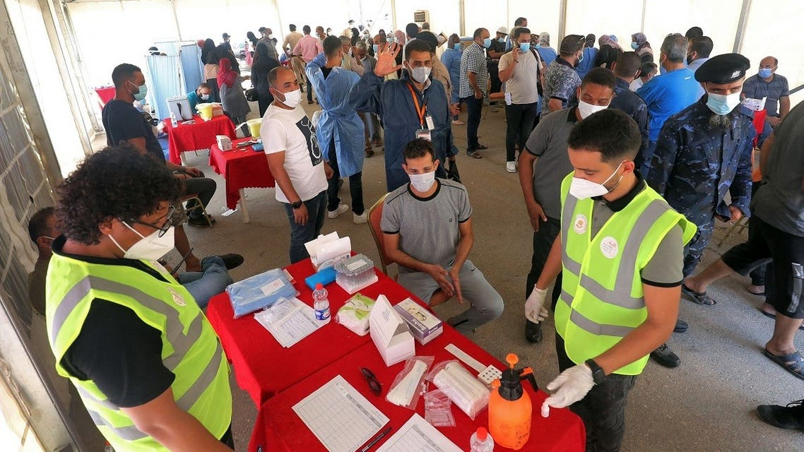 People wait at a make-shift COVID-19 coronavirus vaccination and testing centre erected at the Martyrs' Square of Libya's capital Tripoli on July 24, 2021. (Mahmud Turkia/AFP)