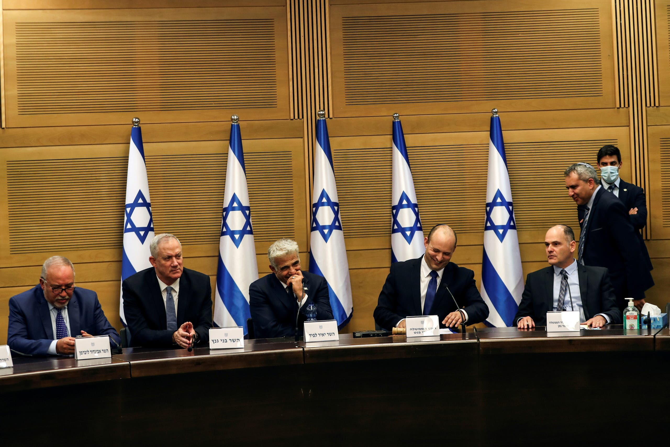 Israeli Prime Minister Naftali Bennett and some of his government attend its first cabinet meeting in the Knesset, Israel's parliament, in Jerusalem June 13, 2021. (Reuters)
