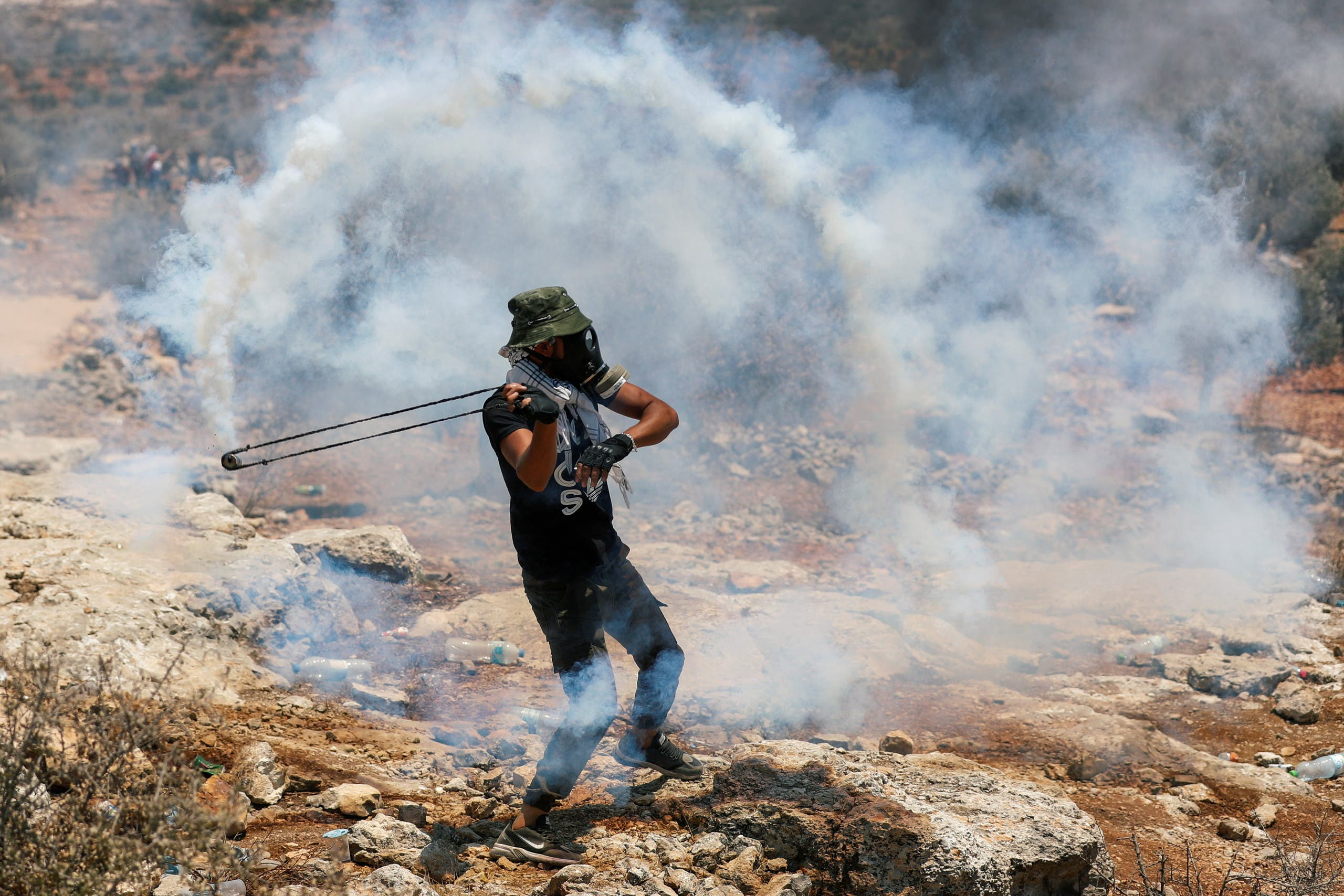 A Palestinian demonstrator uses a slingshot during a protest against Israeli settlements, in Beita, in the Israeli-occupied West Bank July 9, 2021. (Reuters)