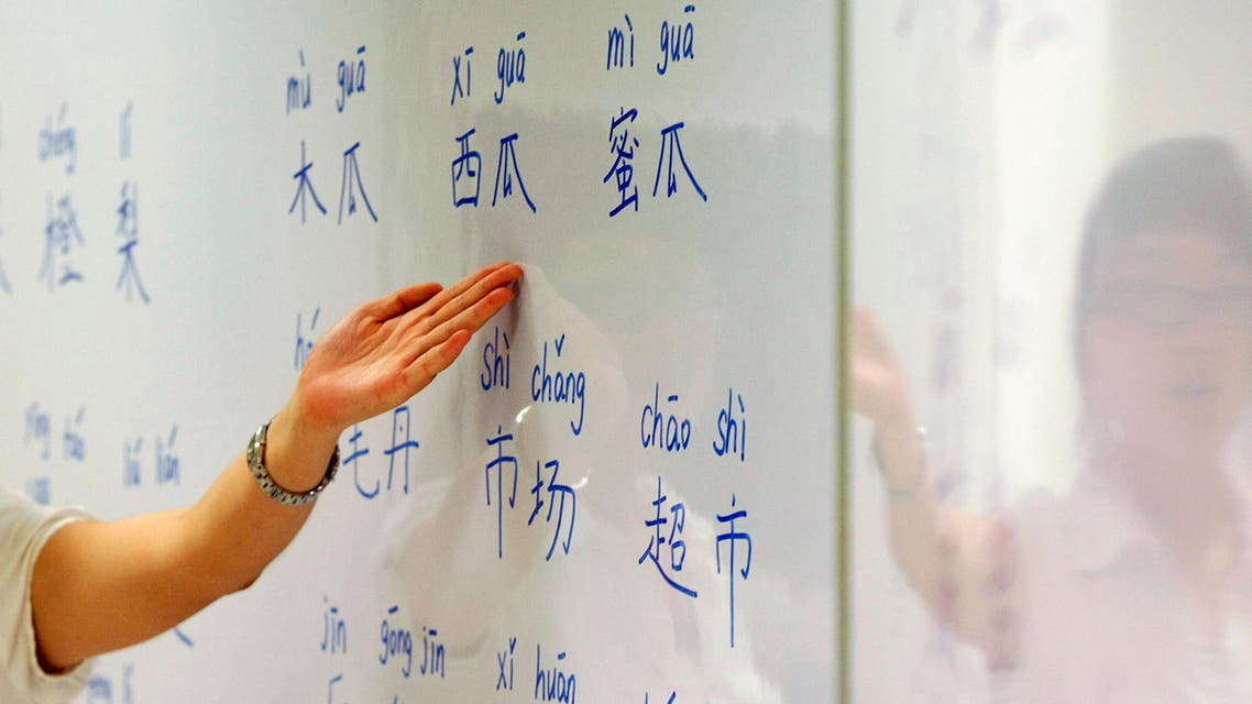 An instructor points out mandarin characters on a whiteboard at a night class for people learning mandarin as a second language in Singapore September 1, 2009. (Reuters)