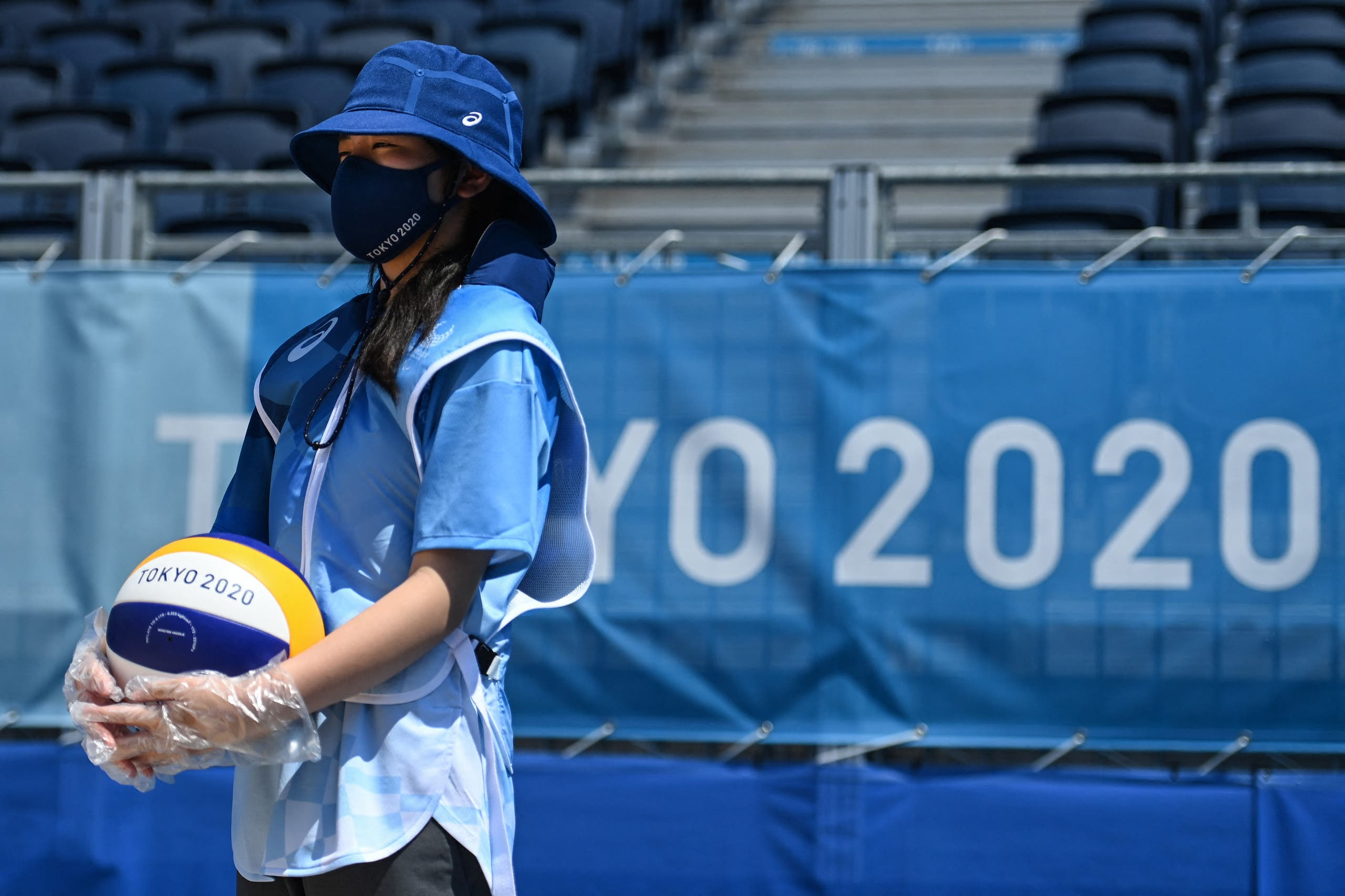 An attendant, wearing plastic gloves, holds a ball before the men's preliminary beach volleyball pool D match between Brazil and Argentina during the Tokyo 2020 Olympic Games at Shiokaze Park in Tokyo on July 24, 2021. (AFP)