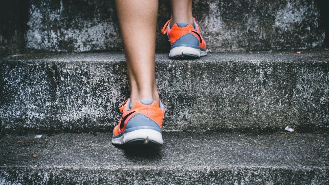 A person exercising by running up stone steps. (Unsplash, Bruno Nascimento)
